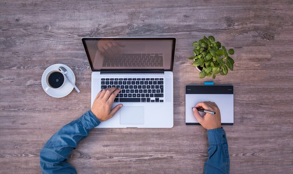 immagine dove è presente un mac book, un caffè, una tavoltta grafica una penna e un ragazzo che lavora presumibilmente un Copywriter